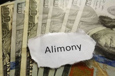 alimony on a piece of paper on top of one hundred dollar bills