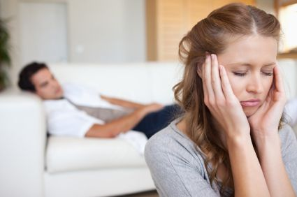 woman upset while husband is on the couch behind her
