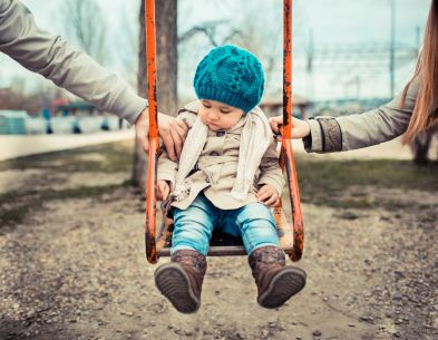 two parents pushing a child on a swing