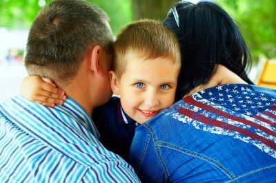 kid smiling to hug his parents