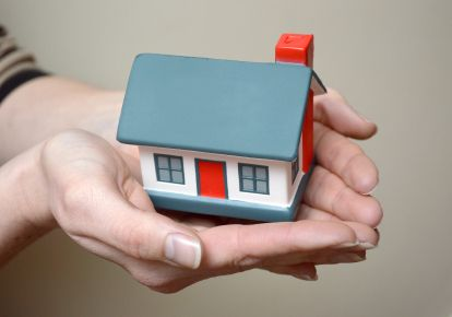 little house in the palm of a woman's hands